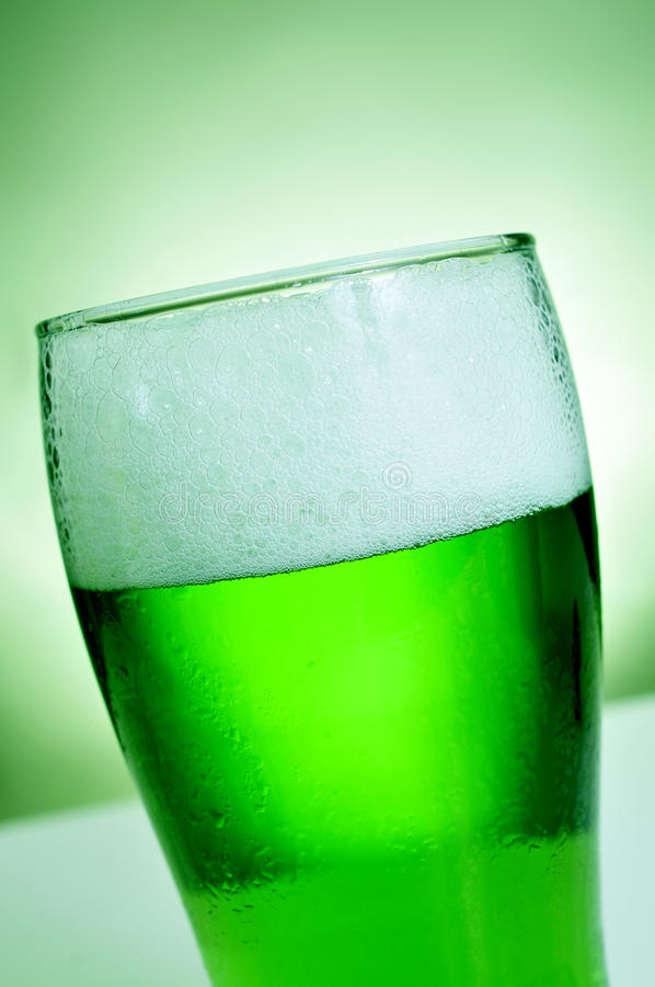 Glass with dyed green beer stock image