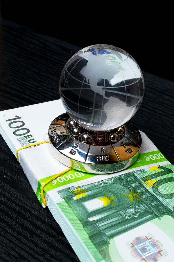 Glass earth with choice and big amount euro cash on the black wooden background. Glass earth with choice and big amount euro cash 500, 100 on the black wooden royalty free stock photos