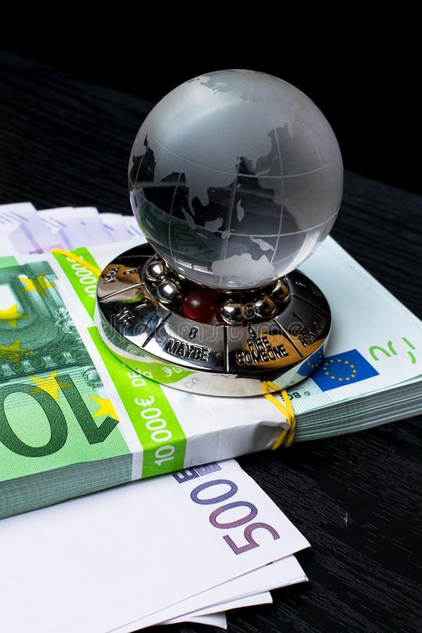 Glass earth with choice and big amount euro cash on the black wooden background. Glass earth with choice and big amount euro cash 500, 100 on the black wooden royalty free stock photo
