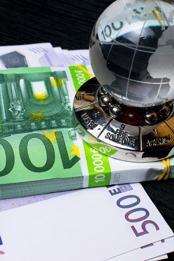 Glass earth with choice and big amount euro cash on the black wooden background. Glass earth with choice and big amount euro cash 500, 100 on the black wooden royalty free stock photography