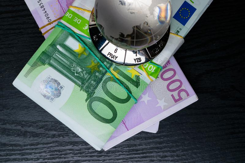 Glass earth with choice yes or no or pray, and big amount euro cash. Glass earth with choice yes or no, and big amount euro cash on the black wooden background stock image