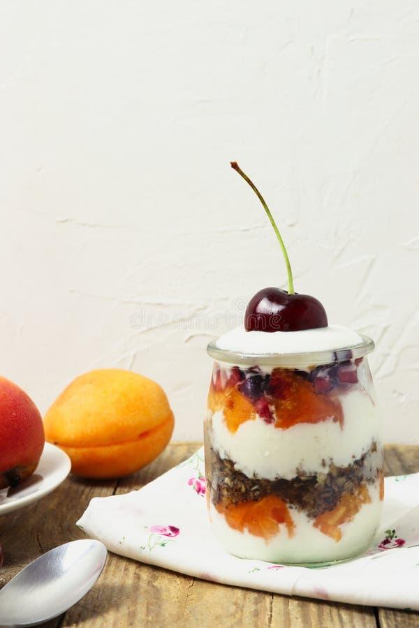 Glass efterrätt som göras av yoghurt, granola, aprikors och körsbär royaltyfri foto