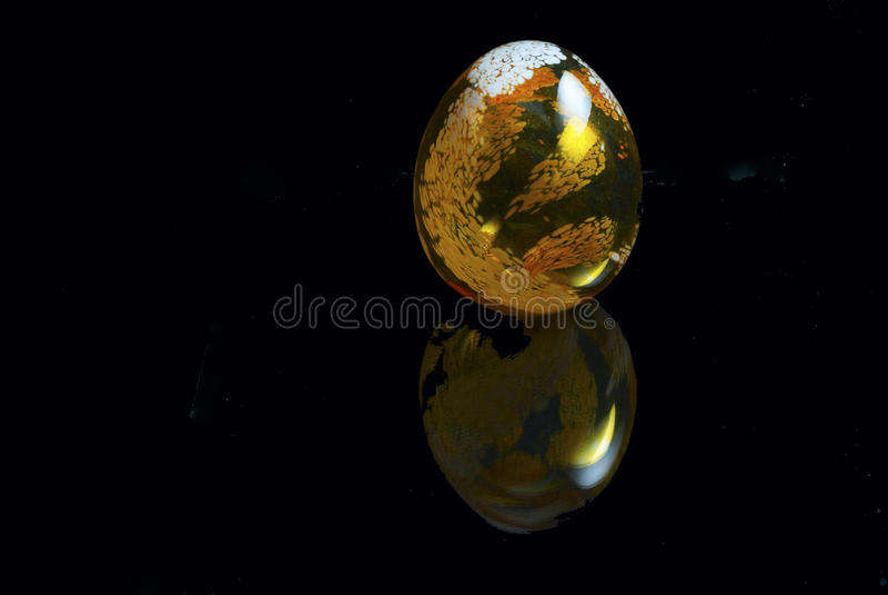 Golden egg. Glass egg on black reflective background stock illustration