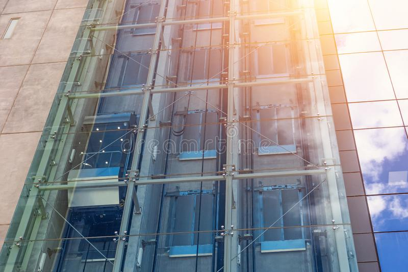 Glass elevators outside the skyscraper building, business architecture.  stock photos