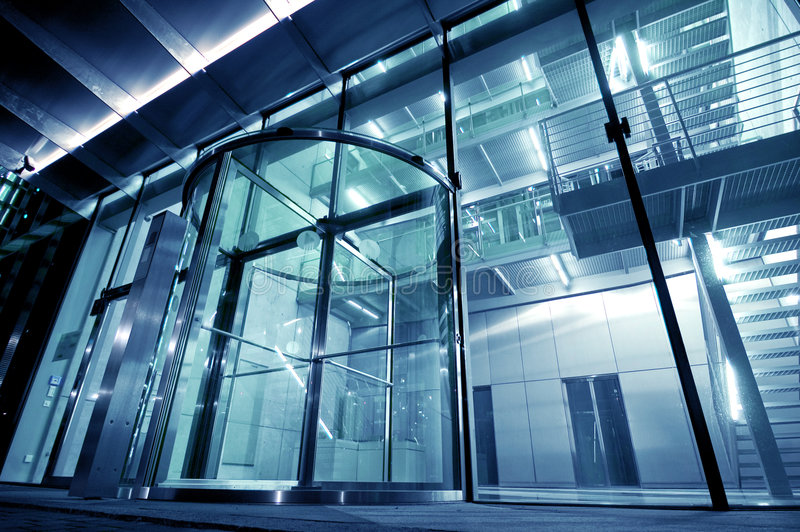 Glass Entrance to Modern Building. All-glass entrance to a large, modern office and business building. Digitally modified in blue tone royalty free stock image