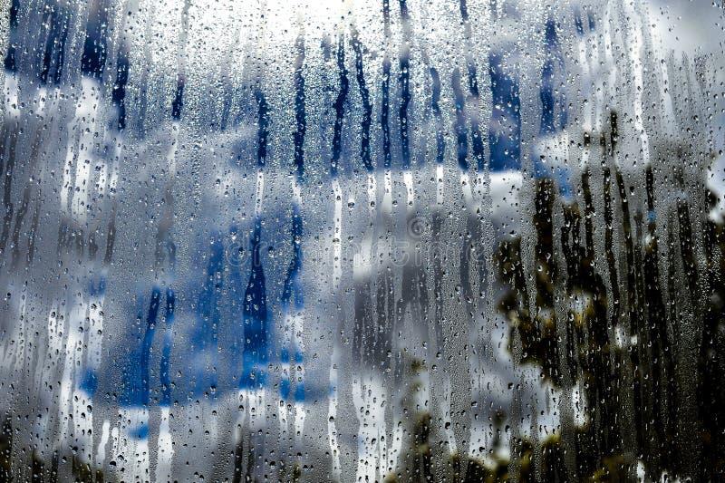 Glass fönster med regn, himmelmoln och solen på bakgrund arkivfoton