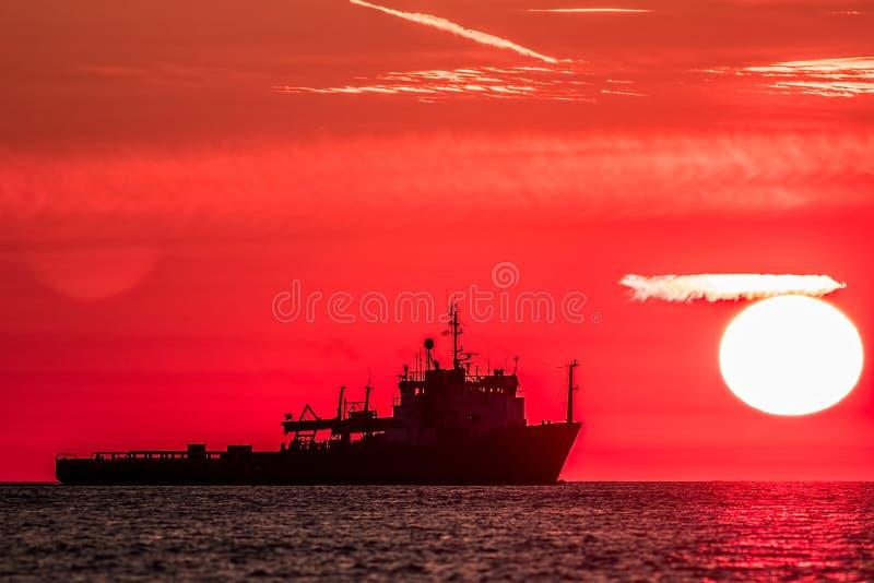 glass förstorande översiktslopp för destination Röd gryning på havet Silhou för fisketrålarefartyg royaltyfria foton