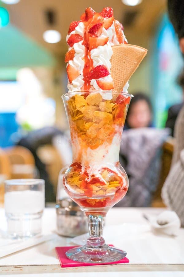 Glass f?r jordgubbeglasscoupe med garneringtornet med piskar kr?m- och jordgubbes?s royaltyfri foto