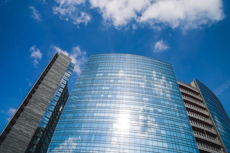 Glass facade of a modern buildings and clouds stock image