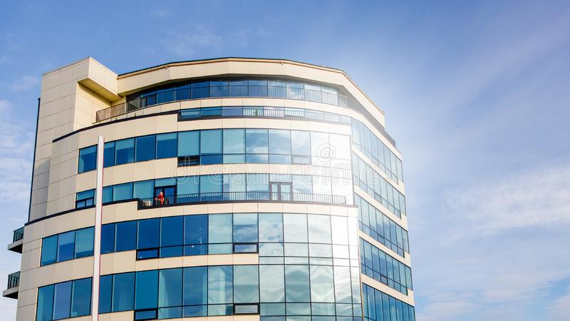 Glass facade of modern multi-storey building with sun glare in windows against blue sky background_ stock image