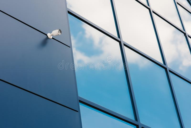 Glass facade of modern office building with security camera. And reflected clouds stock photography