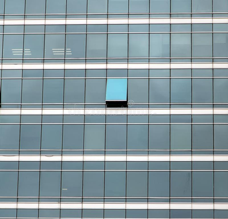 The glass facade of skyscraper. With many identical windows and only one window is different. Same glasses structure of house wall with one exception - open royalty free stock images