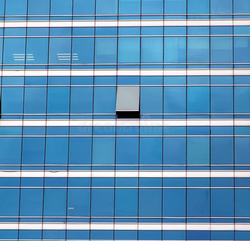 The glass facade of skyscraper. With many identical windows and only one window is different. Same glasses structure of house wall with one exception - open royalty free stock photos