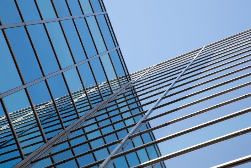 Glass fasad av kontorsbyggnad och reflexioner av blå himmel royaltyfri fotografi