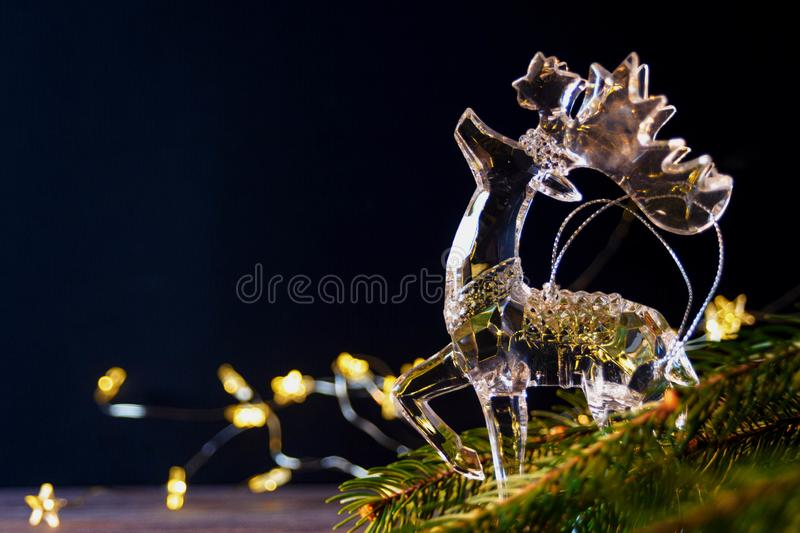 Glass figurine of a deer on a dark background between spruce branches. New Year and Christmas concept. Blurred.  stock image