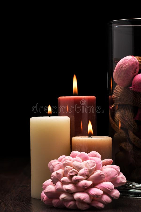 Glass filled with brown, pink and red potpourri with three lit candles on wooden table with black background. Rembrandt lighting royalty free stock photography