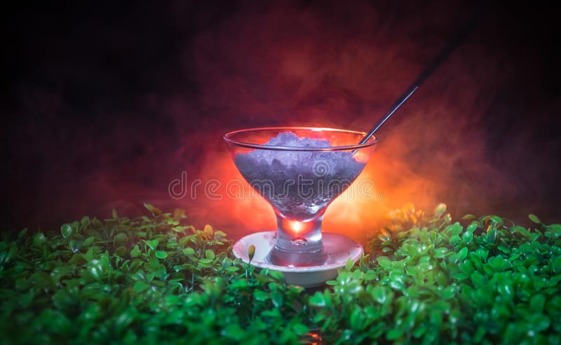 Glass filled with colorful fruit ice cream on dark background with toned light and fog. Selective focus royalty free stock photos