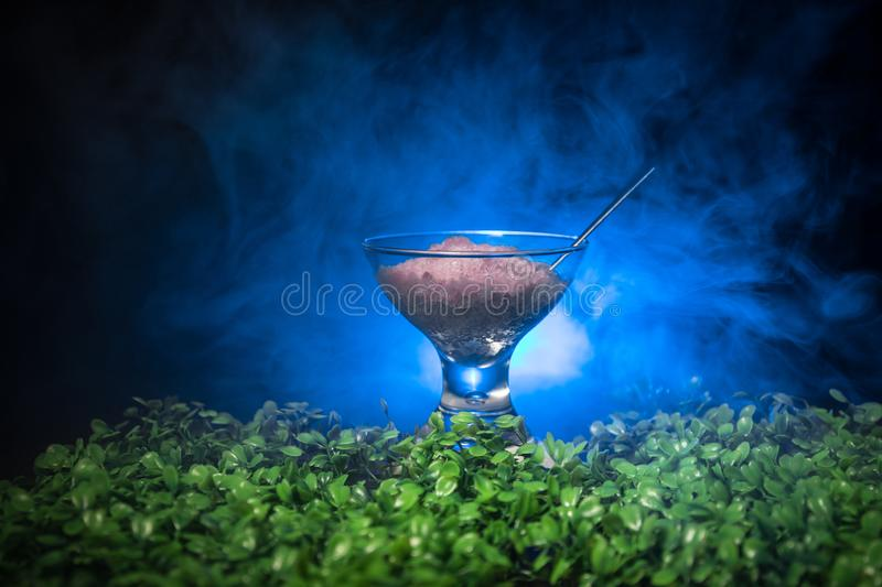 Glass filled with colorful fruit ice cream on dark background with toned light and fog. Selective focus stock photos