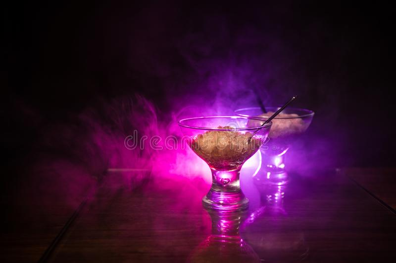 Glass filled with colorful fruit ice cream on dark background with toned light and fog. Selective focus stock image