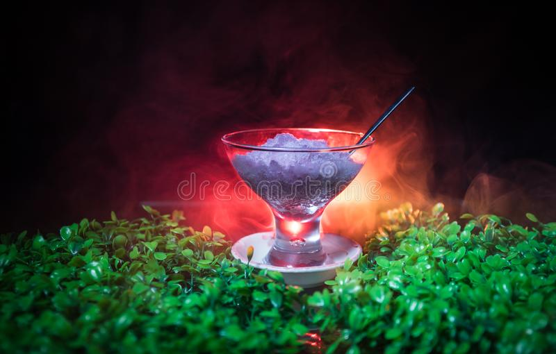 Glass filled with colorful fruit ice cream on dark background with toned light and fog. Selective focus royalty free stock image