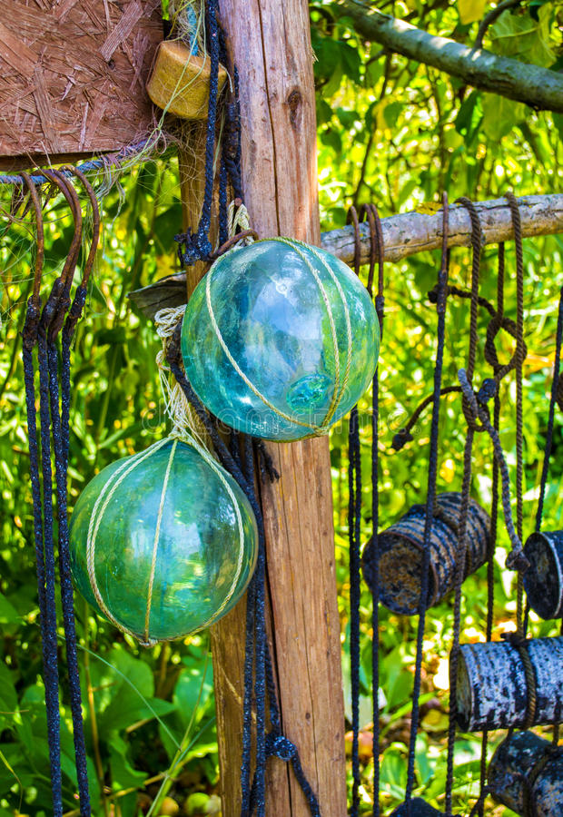 Glass fishing floats with rope knot netting piled royalty free stock photography