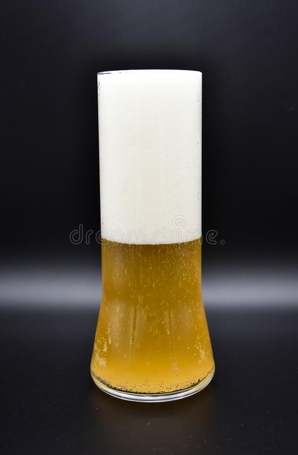 glass flask on black background with yellow liquid and white foam, stock photos