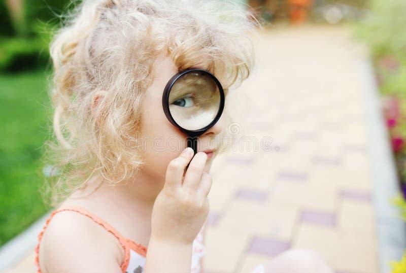 glass flicka little som ser förstora arkivfoton