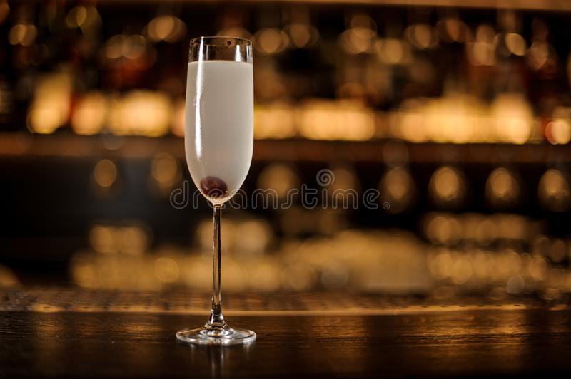 Glass of a French 75 cocktail with berry standing on the bar counter. On the blurred dark and yellow light background royalty free stock photo