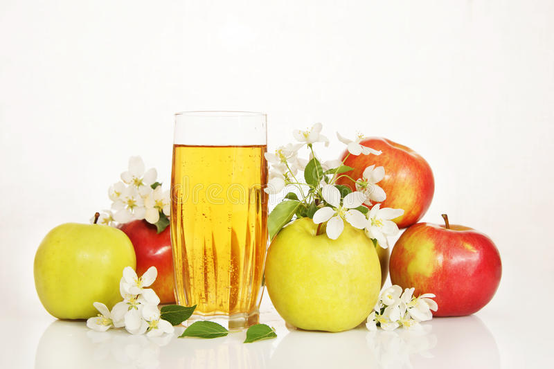 Glass of fresh apple juice with ripe apples and white flowers stock images