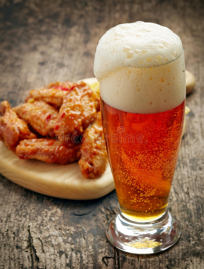 Glass of fresh beer and fried chicken wings. On wooden table royalty free stock photos