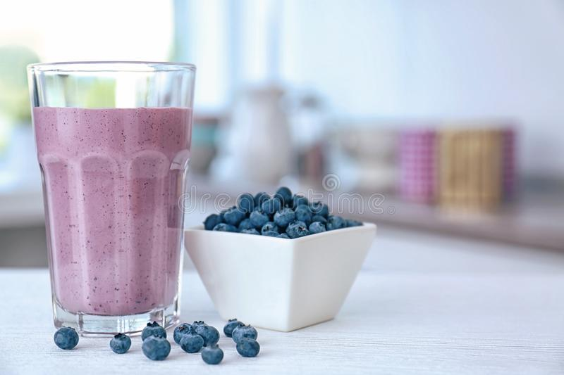 Glass with fresh blueberry smoothie and berries. On kitchen table stock images