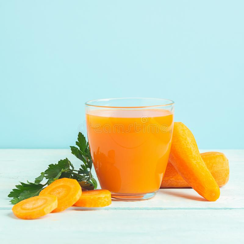 A glass of fresh carrot juice on a wooden blue background. Selective focus. Copy space stock photo