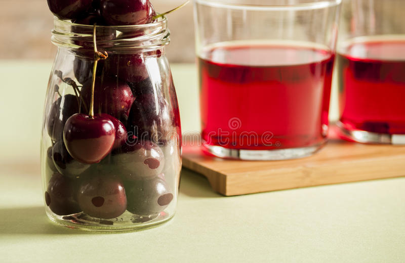 Glass of fresh cherry juice and fresh cherries royalty free stock images