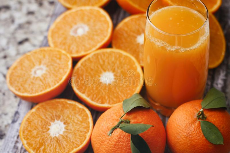 Glass with fresh citrus juice. Halves of tangerines and full fruits with leaves. Wood food stand. stock photos