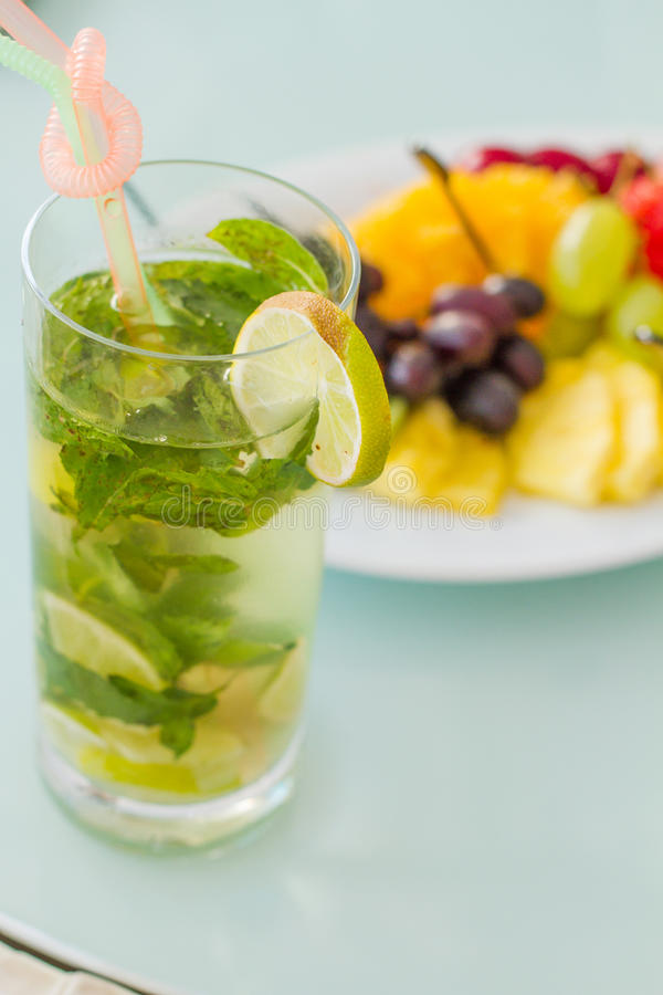 Glass with fresh cocktail lime and mint leafs. Glass with fresh cocktail with lime and mint leafs with fruit on the table on the background royalty free stock photography