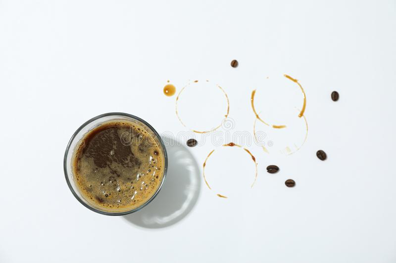 Glass of fresh coffee, coffee beans and rings on white background, space for text. And top view royalty free stock image