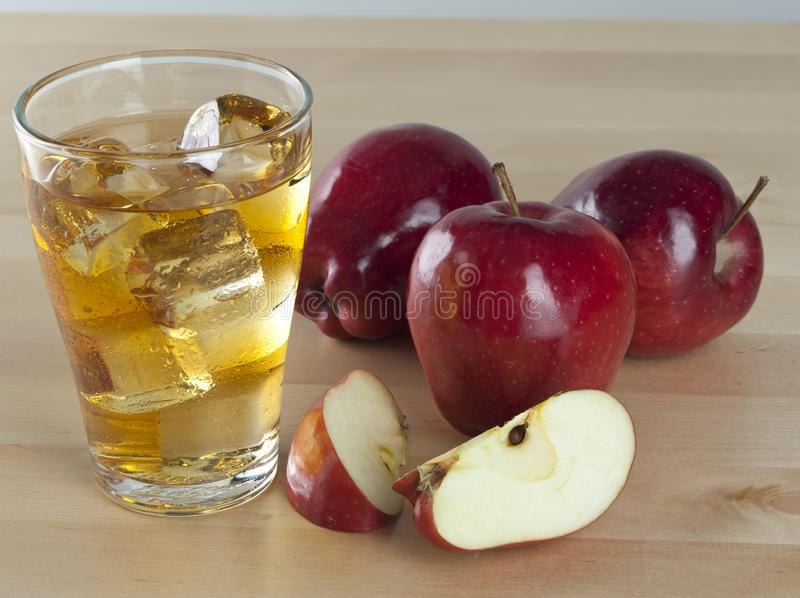 A Glass of Fresh Cold Apple Juice with Ice Beside Apples on A Wooden Table stock image