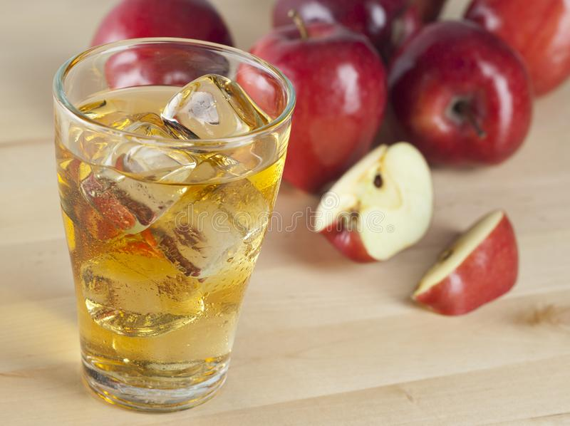 A Glass of Fresh Cold Apple Juice with Ice Beside Apples on A Wooden Table royalty free stock photos