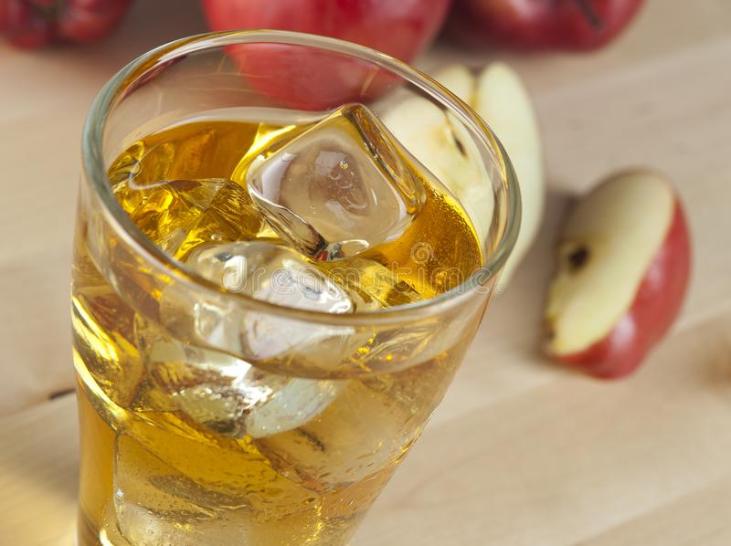 A Glass of Fresh Cold Apple Juice with Ice Beside Apples on A Wooden Table stock photos