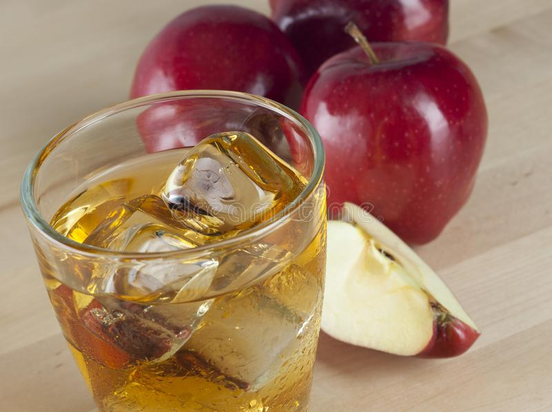 A Glass of Fresh Cold Apple Juice with Ice Beside Apples on A Wooden Table stock photo