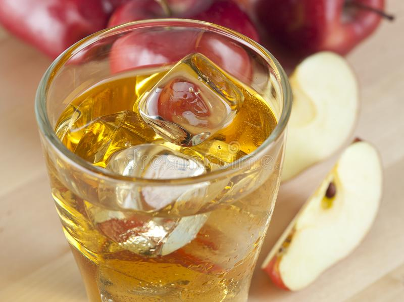 A Glass of Fresh Cold Apple Juice with Ice Beside Apples on A Wooden Table royalty free stock photography