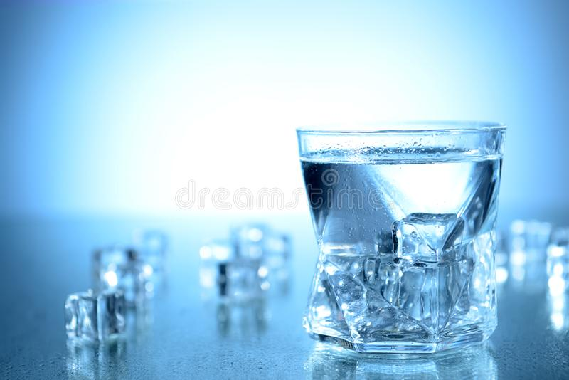 Glass of fresh cool water and ice cubes on table royalty free stock photo