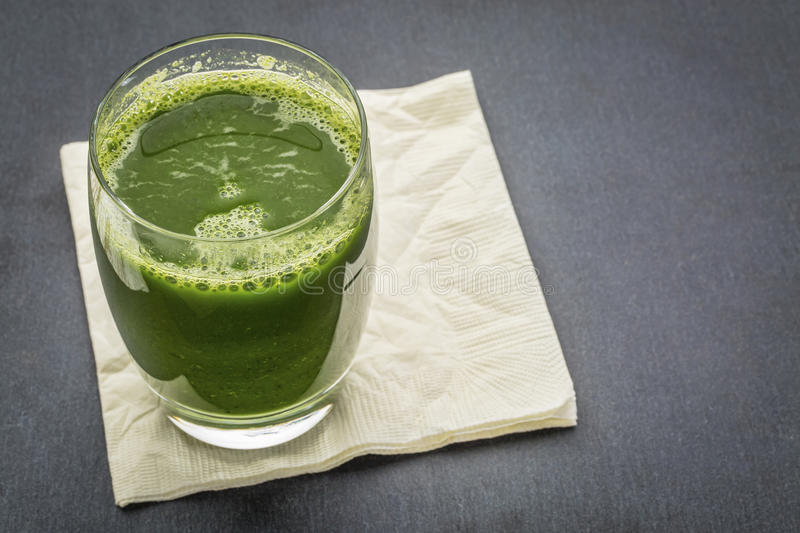 Glass of fresh green juice. Fresh green vegetable juice from cucumber, spinach and cabbage - a glass with napkin on a slate stone background stock photo