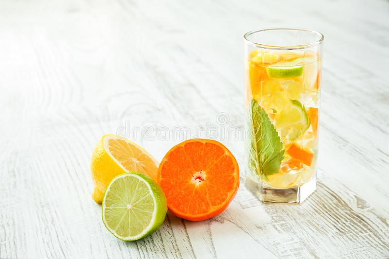 Glass of fresh and healthy summer drink with lemon, lime and tangerine slices, mint leaves and crushed ice on white wooden table royalty free stock photos