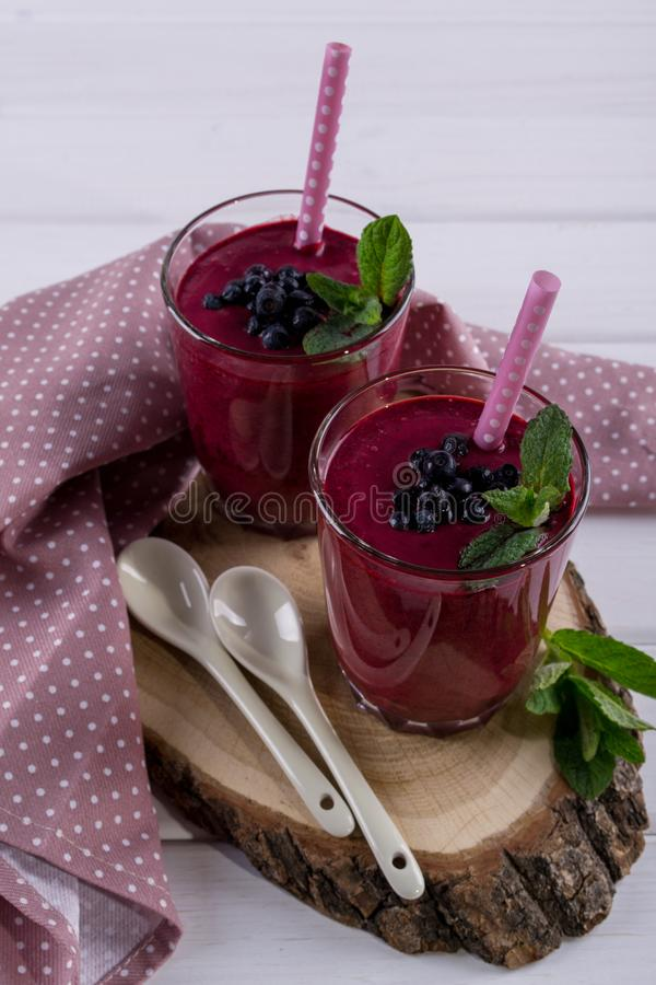 Glass of fresh homemade blueberry smoothie with mint leaf. royalty free stock photo