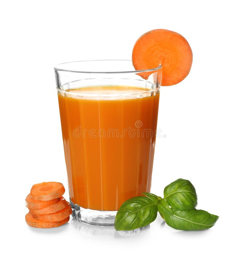 Glass of fresh juice, carrot slices and basil royalty free stock photos