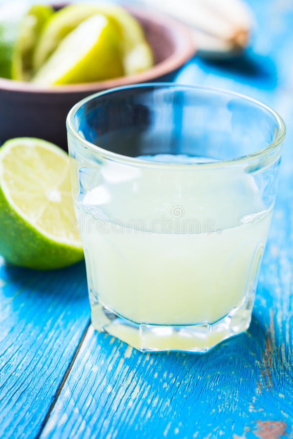 Glass with fresh lime juice on blue wooden background stock image