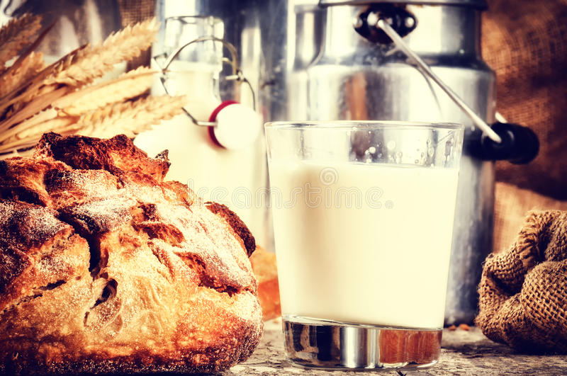 Glass of fresh milk and bread in country setting stock images