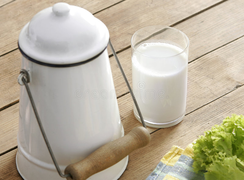 Glass of fresh milk and old milk-churn stock image