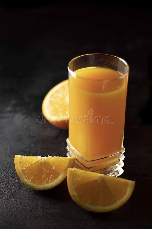 Glass of Fresh Orange Juice on black Table with black Background. - Image stock photo